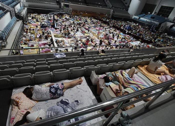 В жару китайские студенты ночуют в огромном спортивном зале