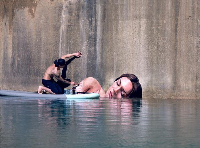Художник рисует, балансируя на серфе