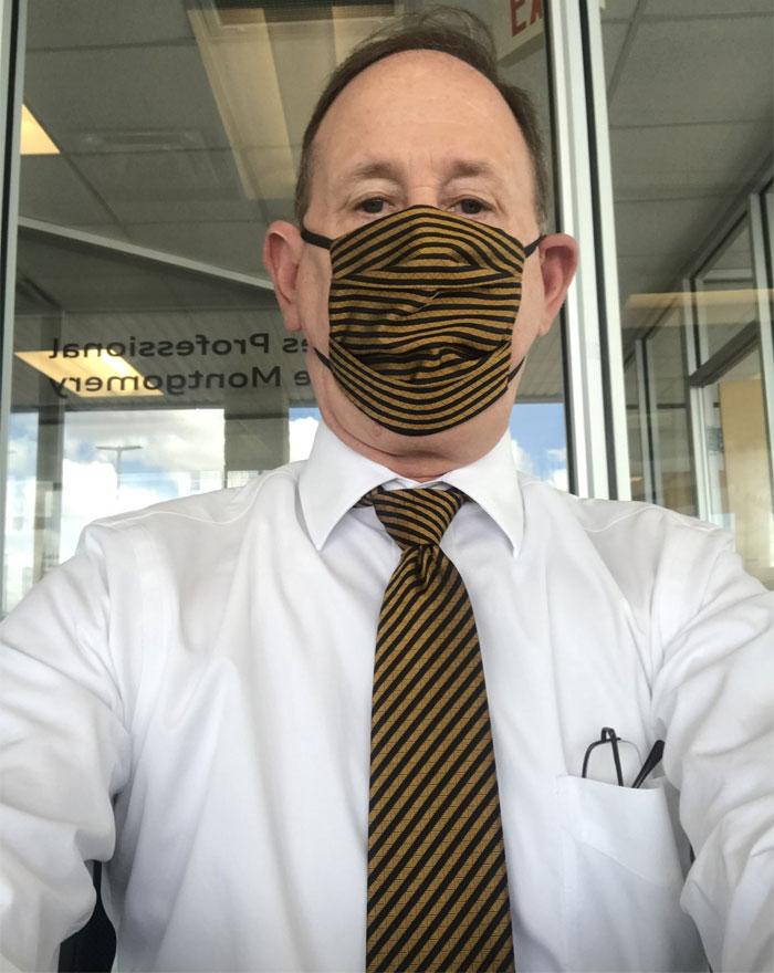 Мужчина подбирает маску под галстук во время эпидемии коронавируса